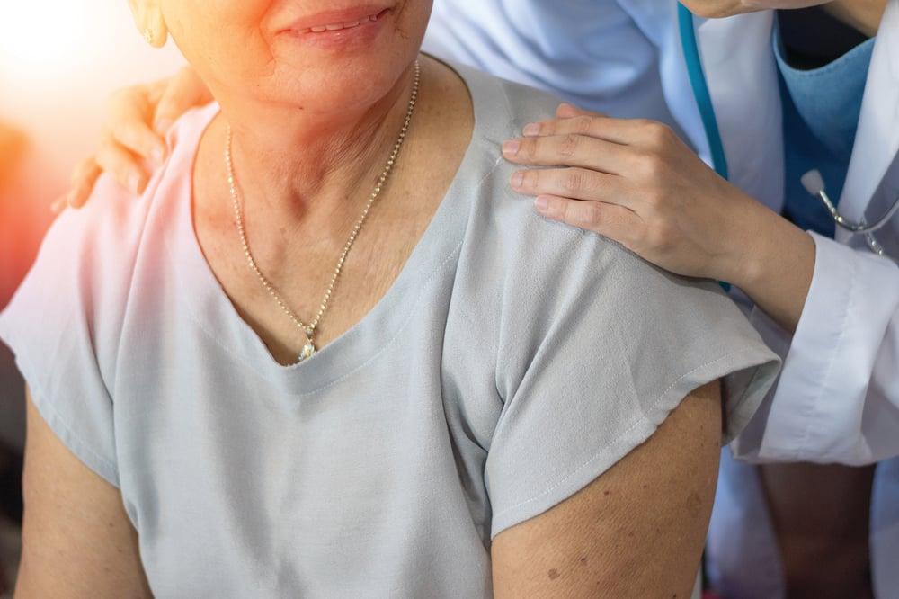 doctor with hands on patient shoulders-1