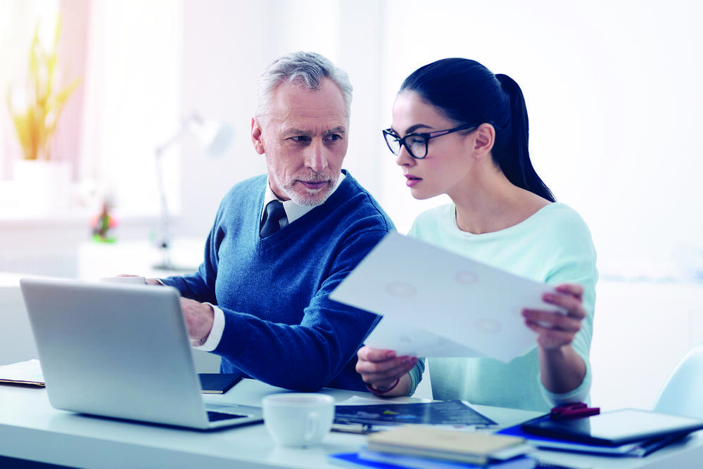 business man and woman on laptop with paper